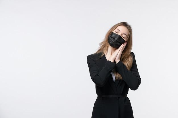 Jovem sonolenta mulher de negócios de terno usando sua máscara médica na parede branca