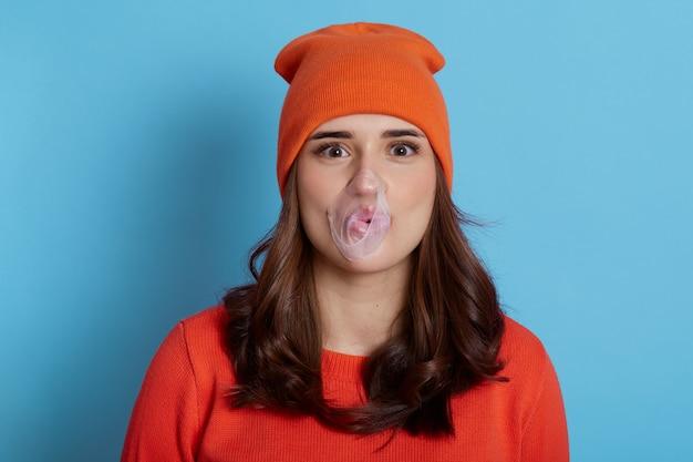 Jovem soprando chiclete isolado em uma garota azul e feliz com cabelo escuro, com estouro de chiclete na boca, vestindo um macacão laranja e boné
