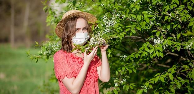Jovem, soprando nariz e espirros em tecido na frente da árvore florescendo. alérgenos sazonais que afetam as pessoas. bela dama tem rinite.