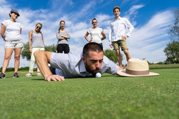 Jovem, soprando uma bola de golfe ao lado de um buraco com pessoas ao redor