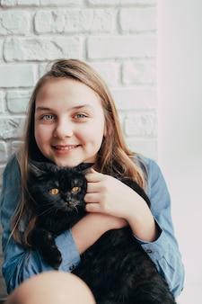 Jovem sorridente abraça um gato preto