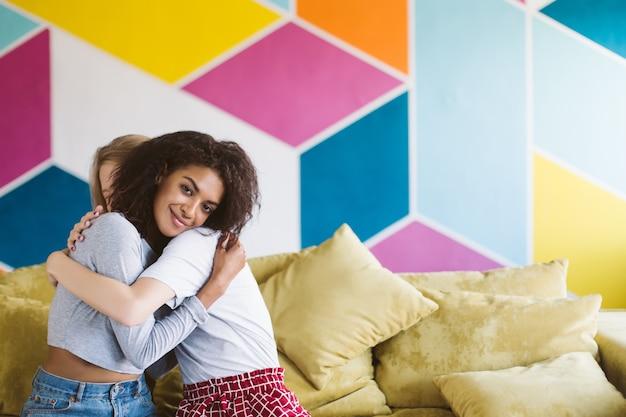 Jovem sorridente afro-americana com cabelo escuro encaracolado abraçando a namorada com ar sonhador e feliz com a parede colorida