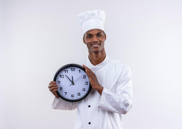 Jovem sorridente afro-americana com uniforme de chef segurando um relógio isolado na parede branca