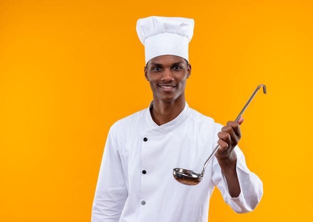Jovem sorridente afro-americana com uniforme de chef segurando uma concha isolada na parede laranja