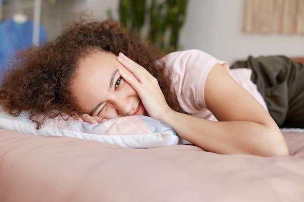 Jovem sorridente afro-americana deitada na cama e toca a bochecha, aproveita o dia ensolarado em casa e parece feliz.