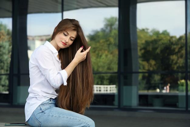 Jovem sorridente alisa seus longos cabelos