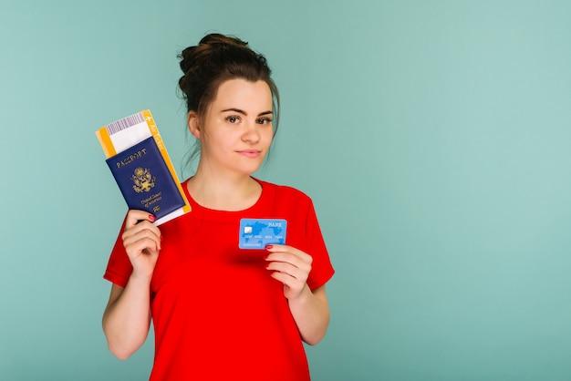 Jovem sorridente animado estudante mulher segurando o bilhete de embarque do passaporte e o cartão de crédito isolado sobre fundo azul. voo de viagem aérea - imagem