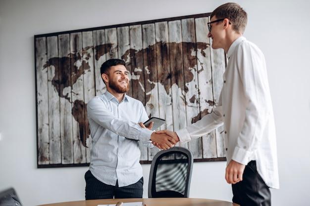 Jovem sorridente, apertando as mãos com seu parceiro de negócios
