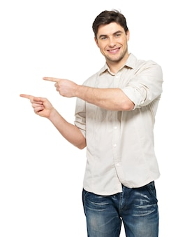 Jovem sorridente aponta com os dedos no lado direito, isolados na parede branca.