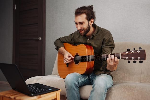 Jovem sorridente aprendendo a tocar violão em casa e olhando para o laptop
