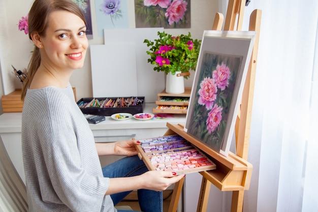 Jovem sorridente artista caucasiana linda garota pinta um quadro com peônias rosa com a ajuda de pastéis secos de giz de cera em uma caixa de madeira. criatividade e conceito de passatempo doméstico