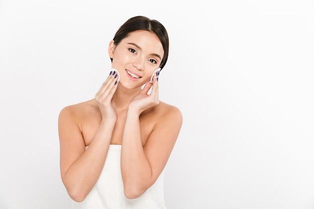 Jovem sorridente asiática remowe maquiagem com esponjas de algodão e
