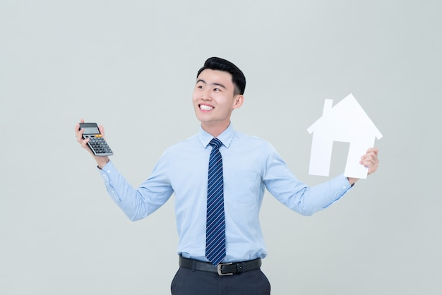 Jovem sorridente asiático masculino agente imobiliário segurando calculadora e recorte de casa
