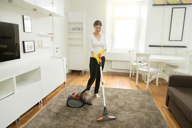 Jovem sorridente, aspirador de pó, limpando o tapete