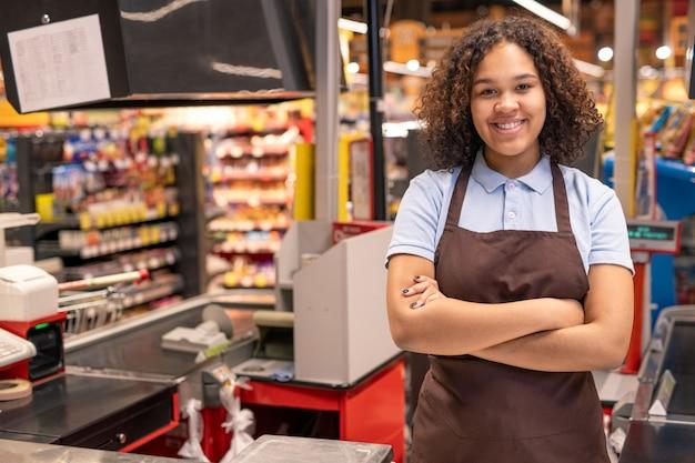 Jovem sorridente assistente de loja ou caixa em traje de trabalho, cruzando os braços no peito, enquanto fica de pé no local de trabalho em ambiente de supermercado