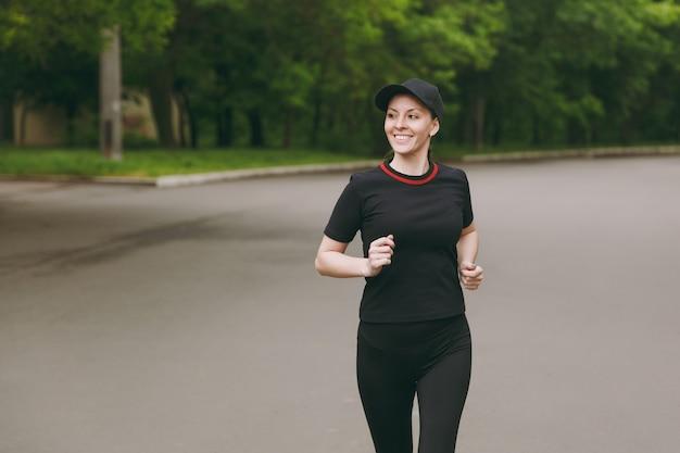 Jovem sorridente atlética linda morena de uniforme preto, treinamento boné, fazendo exercícios de esporte, correndo, correndo, olhando de lado no caminho no parque da cidade ao ar livre