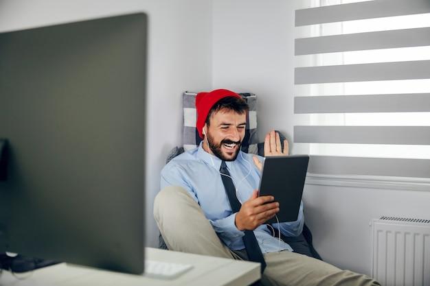 Jovem sorridente atraente barbudo empresário com tampa na cabeça, sentado em seu escritório e tendo a videochamada sobre o tablet.