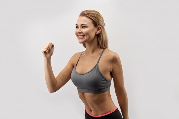 Jovem sorridente atraente com um corpo atlético apto em roupas esportivas, posando com uma expressão alegre e feliz para um retrato em fundo branco isolado
