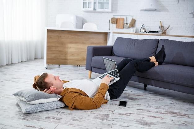 Jovem sorridente atraente e casual sentado no chão em um sofá na sala de estar usando um laptop