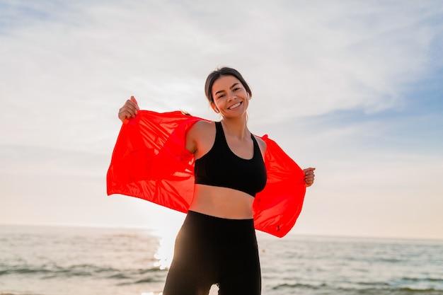 Jovem sorridente atraente magro praticando esportes no nascer do sol da manhã, dançando na praia do mar com roupas esportivas, estilo de vida saudável, ouvindo música em fones de ouvido, vestindo jaqueta corta-vento rosa, se divertindo