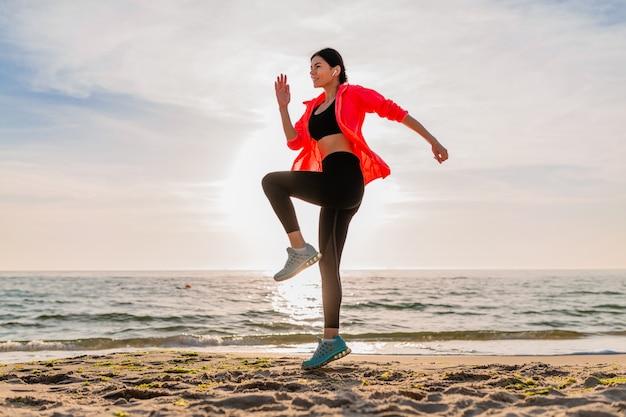 Jovem sorridente atraente magro praticando esportes no nascer do sol da manhã, pulando na praia do mar com roupas esportivas, estilo de vida saudável, ouvindo música em fones de ouvido, vestindo jaqueta corta-vento rosa, se divertindo