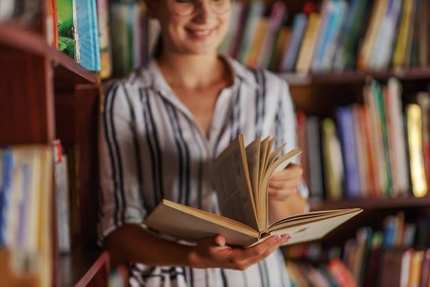 Jovem sorridente atraente universitária apoiando-se nas prateleiras de livros na biblioteca e em busca de material para lição de casa.