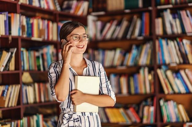 Jovem sorridente atraente universitária com óculos e vestido de pé na biblioteca