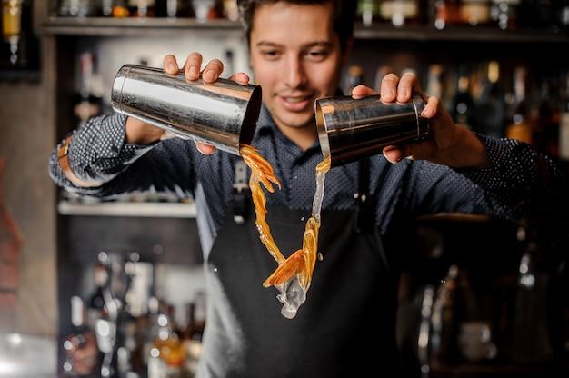 Jovem sorridente barman derramando bebida com fatias de frutas frescas de laranja