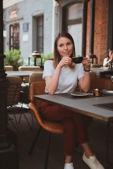 Jovem sorridente bebe café em um café de rua