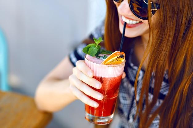 Jovem sorridente bebendo um saboroso coquetel doce, incrível dia relaxante, saborosa limonada, elegante vestido e óculos escuros, terraço ao ar livre.
