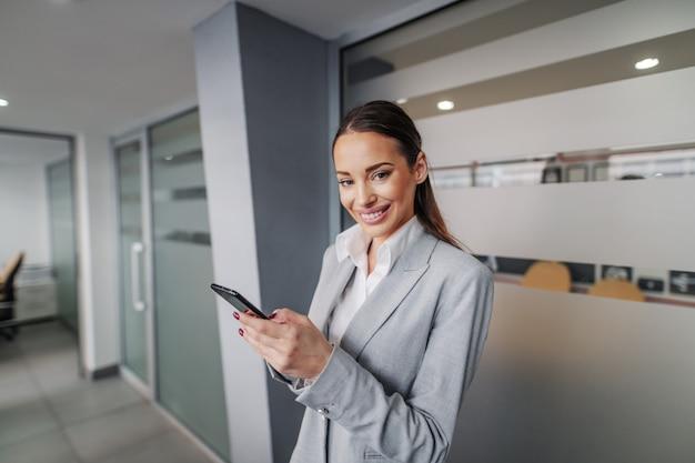 Jovem sorridente bem sucedida linda empresária caucasiana em pé no corredor da empresa corporativa, segurando o telefone inteligente e fazendo uma pausa.