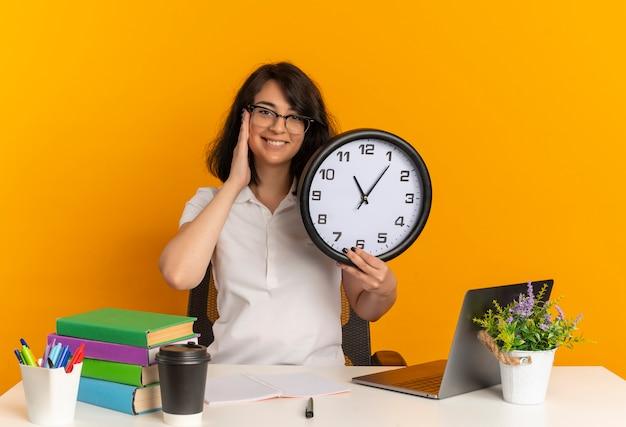 Jovem sorridente, bonita caucasiana colegial de óculos, sentada na mesa com as ferramentas da escola, colocando a mão no rosto, segurando um relógio isolado no espaço laranja com espaço de cópia