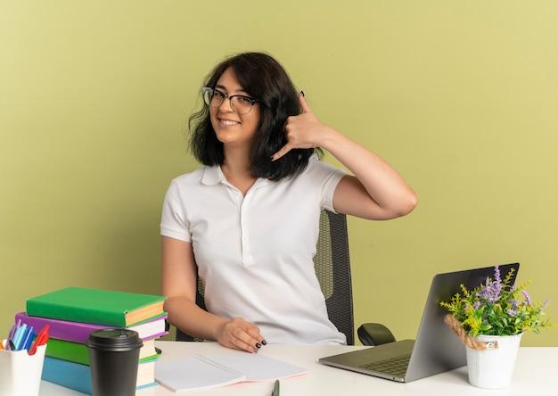 Jovem sorridente, bonita caucasiana colegial de óculos, sentada na mesa com ferramentas da escola, gestos, mão do telefone, sinal verde, com espaço de cópia