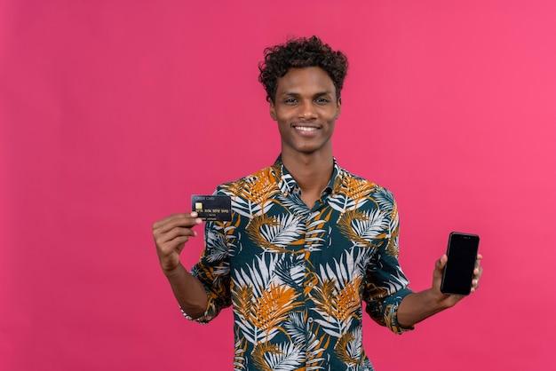 Jovem sorridente, bonito, de pele escura com cabelo encaracolado e camisa estampada de folhas mostrando uma tela de telefone inteligente em branco com cartão de crédito em um fundo rosa