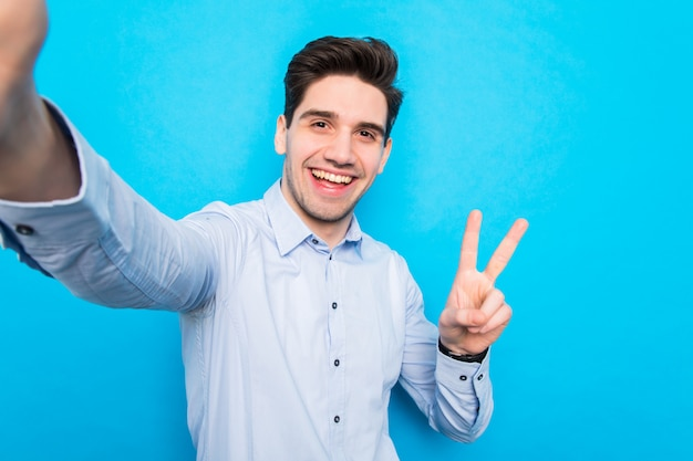 Jovem sorridente bonito está fazendo selfie no smartphone e gesticulando paz no espaço azul