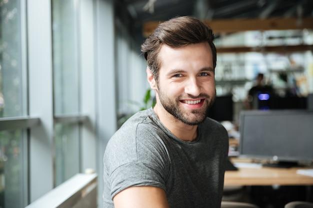 Jovem sorridente bonito sentado no escritório coworking