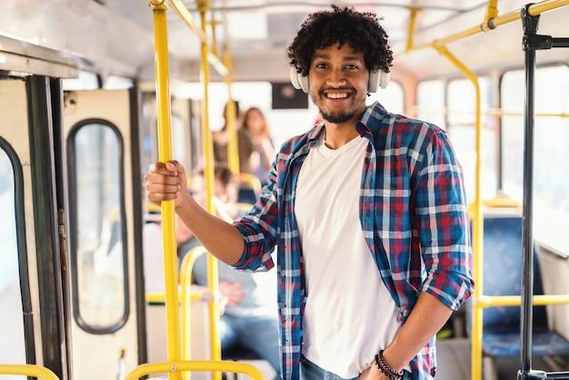 Jovem sorridente cara afro-americana dirigindo em transporte público e ouvindo a música enquanto segura o aperto.