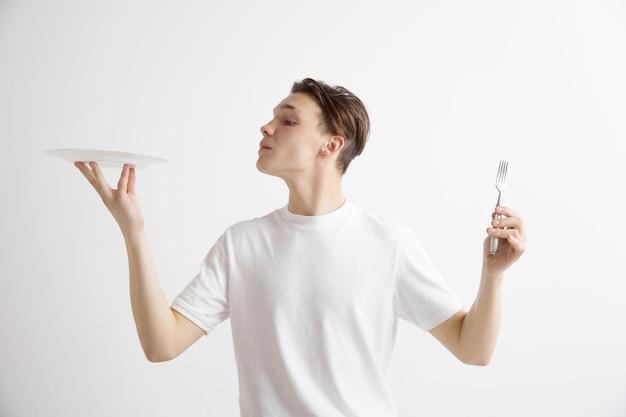 Jovem sorridente cara caucasiano atraente segurando o prato vazio e um garfo isolado no fundo cinza. copie o espaço e simule-se. fundo do modelo em branco.