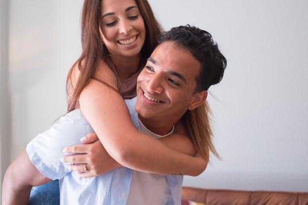 Jovem sorridente carregando uma mulher nas costas e rindo em casa