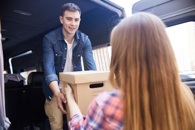 Jovem sorridente carregando van em movimento
