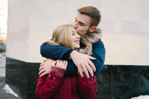 Jovem sorridente casal europeu feliz abraçando no inverno