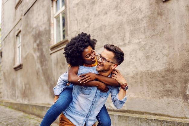 Jovem sorridente casal hippie multicultural cheio de alegria ao ar livre.