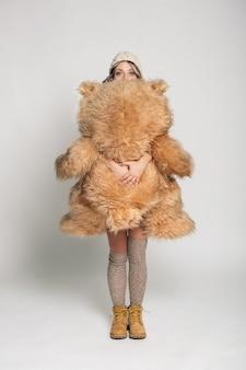 Jovem sorridente casual em roupas de malha, segurando o grande urso de pelúcia macio