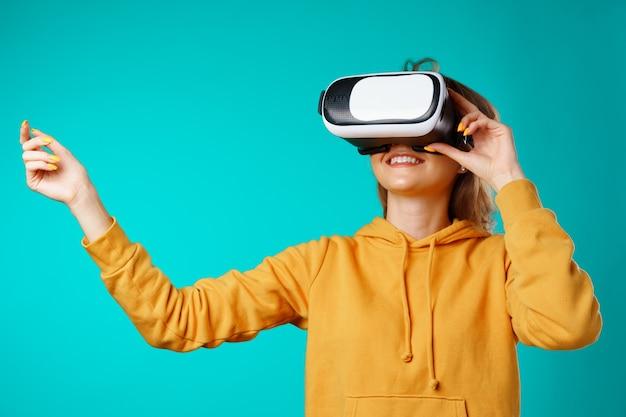 Jovem sorridente casual usando óculos de realidade virtual contra o azul