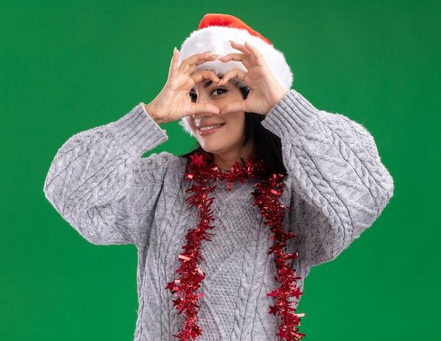 Jovem sorridente caucasiana com chapéu de natal e guirlanda de ouropel no pescoço, olhando para a câmera fazendo um sinal de coração na frente do olho isolado no fundo verde