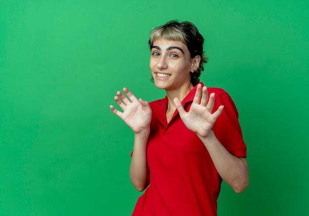 Jovem sorridente caucasiana com corte de cabelo de duende mostrando as mãos vazias isoladas em um fundo verde com espaço de cópia