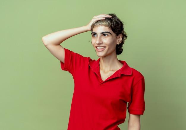 Jovem sorridente caucasiana com corte de cabelo de duende olhando para o lado, colocando a mão na cabeça isolada sobre fundo verde oliva