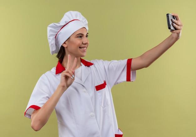 Jovem sorridente caucasiana cozinheira com uniforme de chef olha para o telefone e faz gestos com a mão da vitória sinal verde com espaço de cópia