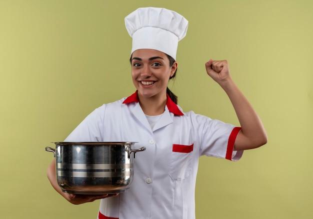 Jovem sorridente caucasiana cozinheira com uniforme de chef segura a panela e levanta o punho isolado na parede verde com espaço de cópia