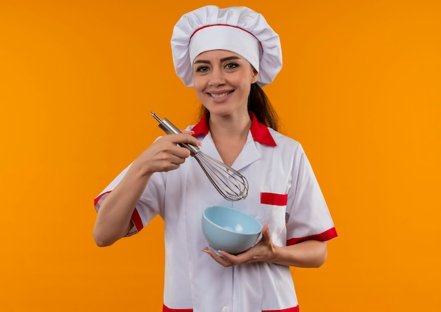 Jovem sorridente caucasiana cozinheira com uniforme de chef segura um batedor e uma tigela isolada na parede laranja com espaço de cópia